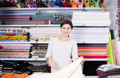 Seller showing white fabric. Smiling girl seller showing white fabric at drapery shop Stock Images