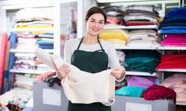Seller showing white fabric. Young woman seller displaying white fabric at drapery shop Royalty Free Stock Image