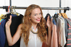 Seller shows clothes hung on hangers Stock Photos