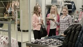 The seller shows goods to two girls. In shop stock footage