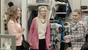 The seller shows goods to two girls. In shop stock video footage