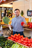 Seller shows vegetables. Smiling seller shows vegetables in shop.  Boxes with fruits and vegetables on the background Stock Photos