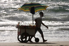 Seller of slush on the beach. A peddler at the beach with a shopping cart full of products to prepare the slush / beach and sea / activities typical of many Stock Images