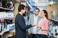 Seller and smiling buyers at household appliances section Stock Photography