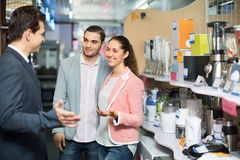 Seller and smiling buyers at household appliances section. Of supermarket Stock Photo