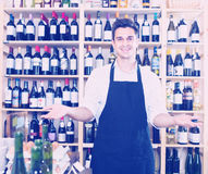 Seller standing in alcohol section. Portrait of male seller in uniform standing in alcohol section in store Royalty Free Stock Photo
