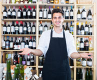 Seller standing in alcohol section Royalty Free Stock Image