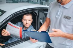 Seller stands at white car and holds tablet in hands. He point on it. Another man sits in car and holds insurance paper. Seller stands at white car and holds stock images