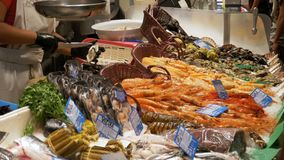 The Seller at the Store Counter with Seafood in La Boqueria Fish Market. Barcelona. Spain. Showcase with various exotic seafood, fish, crabs, clams and more stock footage