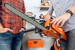 The seller in the store shows the customers a chainsaw. A young couple came to the garden tools store to buy equipment for gardening stock image