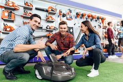 The seller in the store shows the customers a vacuum cleaner. Stock Image