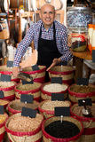 Seller taking dried beans with scoop from basket Royalty Free Stock Images