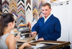 seller talking to customer. american  men seller talking to customer in picture framing studio Royalty Free Stock Image