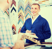 seller talking to customer. cheerful men seller talking to customer in picture framing studio Stock Photography
