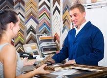 Seller talking to customer. Smiling american men seller talking to customer in picture framing studio Stock Photo