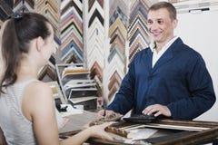 Seller talking to customer. Smiling men seller 40s talking to customer in picture framing studio Royalty Free Stock Photos