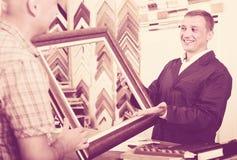 seller talking to customer. Smiling men seller talking to customer in picture framing studio Royalty Free Stock Image