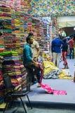 The seller of textiles in the store. DUBAI, UAE - DECEMBER 4, 2017: The seller of textiles in the store Royalty Free Stock Photos
