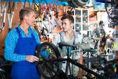 Seller in uniform repairing bicycle. Man seller in uniform repairing and holding bicycle in sport hypermarket Royalty Free Stock Image