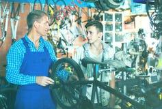 Seller in uniform repairing bicycle. Man seller in uniform repairing and holding bicycle in sport hypermarket Stock Photography