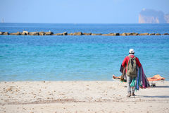 Seller walking on the beach in Alghero shore Royalty Free Stock Images