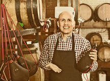 Seller wearing apron and holding spanish bota bag for wine Stock Image