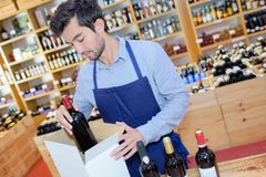 Seller wearing apron preparing box with bottles in wine store. Wine Stock Images