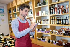 Seller wearing apron writing on clipboard in wine store. Wine Stock Images