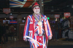 Seller wears uniform symbolizing English flag at entrance of shop Cool Britannia. In background car painted in color of British fl Stock Photography