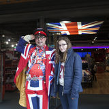 Seller wears uniform symbolizing English flag at entrance of shop Cool Britannia. In background car painted in color of British fl Stock Images