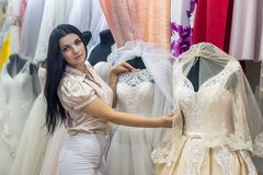 Seller in wedding salon demonstrating dresses for bride. Seller in wedding salon demonstrating dresses for bride royalty free stock images