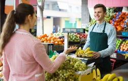 Seller weighing bananas Royalty Free Stock Photography
