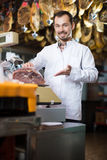 Seller weighing meat. Smiling man seller weighing on scales piece of meat in butcher's shop Stock Photography