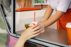 Seller through the window gives the buyer a glass of soft cream ice cream. Street Trading Royalty Free Stock Photo