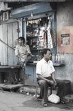 The seller of a window-sized convenience store waits for customers in a street of Kolkata, India. Another man sits by on a stool stock images