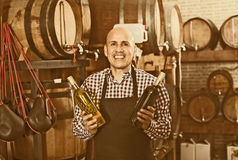 Seller in wine house. Friendly mature seller standing with wine bottles in hands in wine house Stock Images