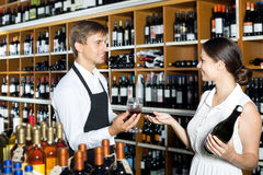 Seller in a wine house and visitor. Young men seller wearing uniform giving to cheerful women customer try glass of wine in wine house. Focus on the man Royalty Free Stock Photo