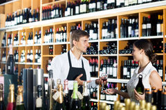 Seller in a wine house and visitor. Young men seller wearing uniform giving to pretty women customer try glass of wine in wine house Stock Photo
