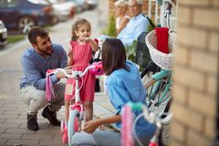 Seller woman helping family to shopping new bicycle for little girl. Seller women helping family to shopping new bicycle for little girl in sport store royalty free stock image