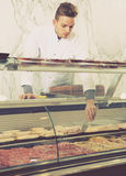 Seller in working clothes taking raw meat Royalty Free Stock Photos