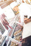 Seller in working clothes taking raw meat Royalty Free Stock Images
