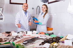 Seller and young assistant offering fresh fish in shop Royalty Free Stock Photos