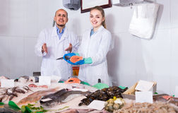 Seller and young assistant offering fresh fish in shop Stock Images