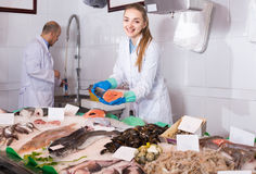 Seller and young assistant offering fresh fish in shop Royalty Free Stock Photography