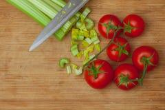 Sellerie und Tomaten auf einem Schneidebrett lizenzfreie stockbilder