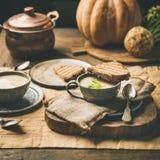 Selleriecremesuppe, Toast, frischer Kürbis am Hintergrund, quadratische Ernte stockfoto