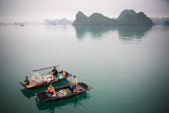 Sellers in Halong Bay, Vietnam. Woman and kids selling out of a boat in Halong Bay, Vietnam Royalty Free Stock Photography
