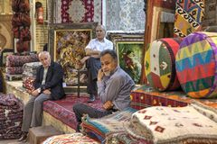 Sellers of Persian rugs in the carpets shop, Shiraz, Iran. Fars Province, Shiraz, Iran - 19 april, 2017: Three mature Iranian men are in the sales department of Royalty Free Stock Photos