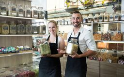 Man and woman sellers posing with banks of dried herbs in store royalty free stock image