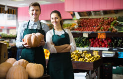 Sellers posing with big pumpkin Royalty Free Stock Images